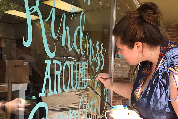 Mizzou alumna Beth Snyder painting hand lettering on a store window