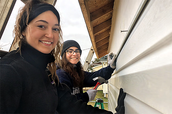 Kelsey Inglis and Kelsey Inglis and Dominique Verdeschi on ladders helping to build a home for the Habitat for Humanity project in Farmington, MO.