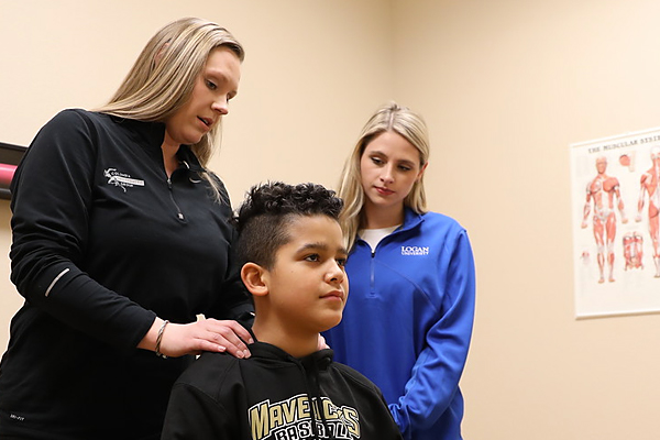 Kara Conroy watches as her internship instructor Brittany Overman Ramirez demonstrates chiropractic care on a young boy.