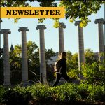 Newsletter. Student walking around Columns on Francis Quadrangle