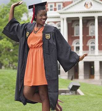 Student wearing cap and gown poses in front of Jesse Hall
