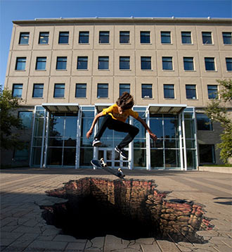 student on skateboard jumping over mural of large hole in sidewalk