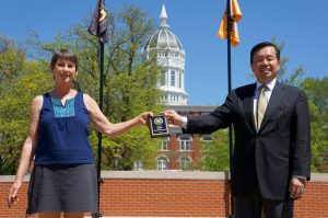 A photo of Teresa Hall receiving an award from President Choi