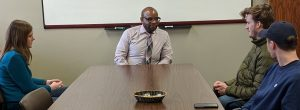 A photo of Professor Trevon Logan meeting with students