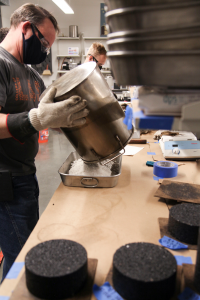 A photo of Mizzou Asphalt Pavement and Innovation Lab staff preparing a plastic waste pavement mixture for testing.